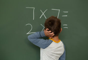 Rear view of Caucasian schoolboy doing math on greenboard in a classroom at elementary school
