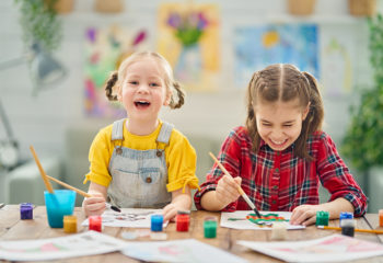 Happy kids are painting at home. The girls are being creative work sitting at the desk.