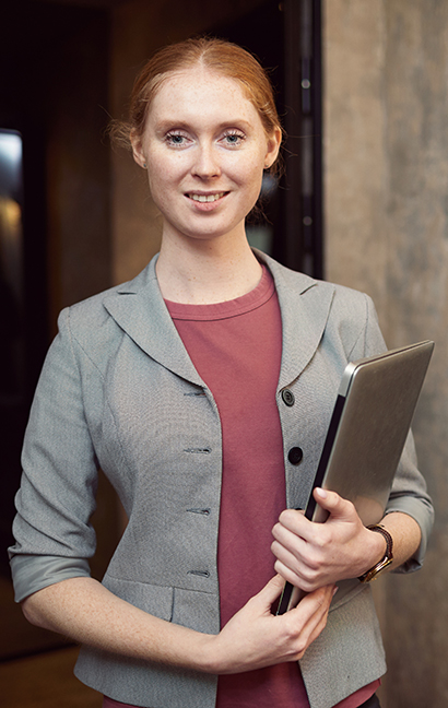 Portrait of young red haired manager holding laptop and looking at camera while working at office